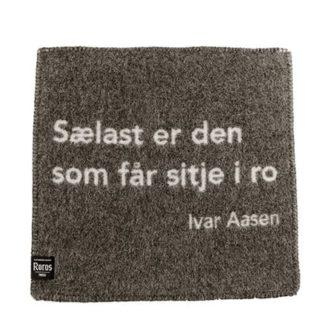 Sitjeunderlag i ull, med sitat av Ivar Aasen